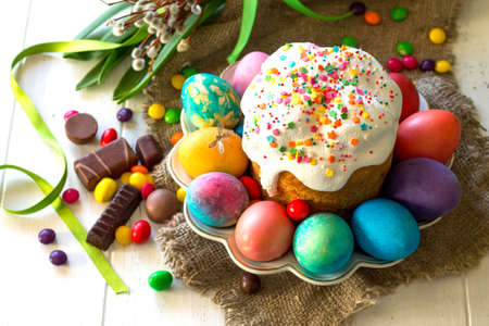 Festive composition in rustic style, Easter meal Breakfast. Easter cake and painted eggs on white wooden table.