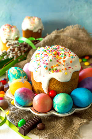 Festive composition in rustic style, Easter meal Breakfast. Easter cake and painted eggs on white wooden table. Copy space.