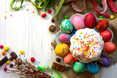 Festive composition in rustic style, Easter meal Breakfast. Easter cake and painted eggs on white wooden table. Top view flat lay background. Copy space. Stock Photo
