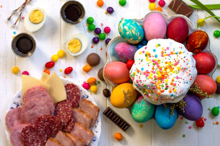 Festive composition in rustic style, Easter meal Breakfast. Easter cake and painted eggs on white wooden table. Top view flat lay background.