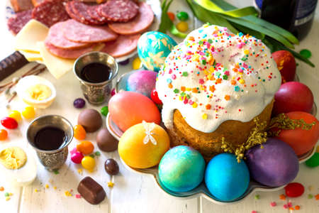 Easter meal Breakfast. Easter cake, painted eggs and delicious delicatessen on white wooden table.