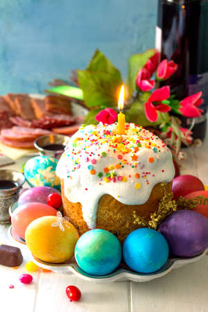 Easter meal Breakfast. Easter cake, painted eggs and delicious delicatessen on white wooden table. Copy space.