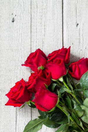 Wedding or Valentines Day, Mother day card. Beautiful blooming Red roses on wooden board. Top view flat lay background. Copy space. Stock Photo