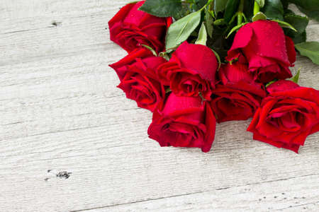 Wedding or Valentines Day, Mother day card. Beautiful blooming Red roses on wooden board. Copy space.