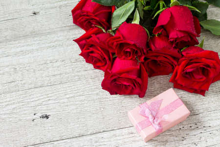 Wedding or Valentines Day, Mother day card. Beautiful blooming Red roses and gift box on wooden board. Copy space.