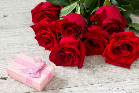 Wedding or Valentines Day, Mother day card. Beautiful blooming Red roses and gift box on wooden board. Stock Photo