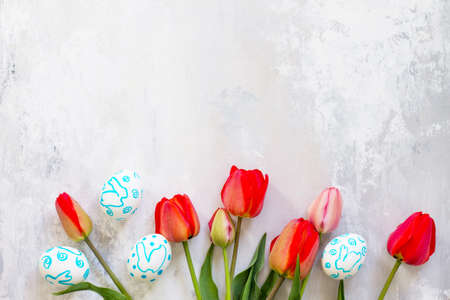 Easter table setting with tulips flowers and Easter eggs. Holidays background. Top view flat lay background. Copy space.