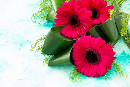 Mother's Day background or greeting card. Bouquet Red Flowers of gerbera on a turquoise stone table. Copy space.