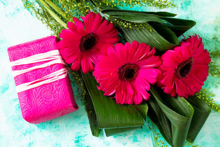 Mother's Day background or greeting card. Bouquet Red Flowers of gerbera and a present on a turquoise stone table.