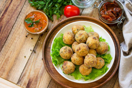Arancini. Italian Rice Balls with Mozzarella and Sun-dried tomatoes, with tomato sauce on wooden table. Top view flat lay background. Copy space.