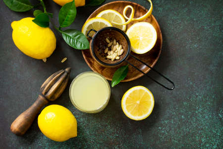 Cold drink with freshly squeezed lemon juice and fresh lemons on a dark stone table. Top view flat lay background with copy space.