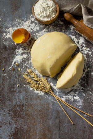 Dough, baking background. Raw dough ball for bread or pizza on a dark table. Copy space.