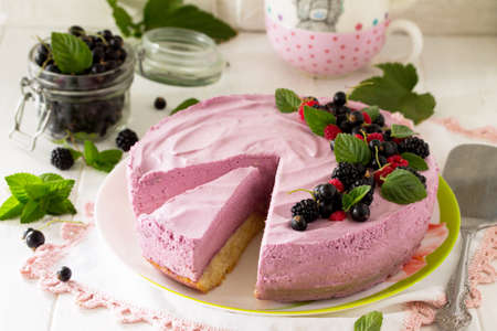 Cake with Black Currant Cream, Souffle and Biscuit on the white kitchen table. Stock Photo