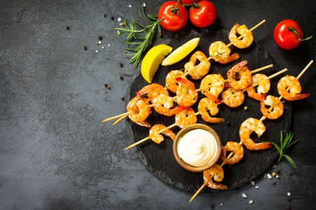 Grilled seafood. Delicious Grilled shrimps with spice, lemon and sauce served on a slate board. Seafood. Top view flat lay background.
