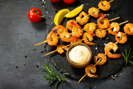 Grilled seafood. Delicious Grilled shrimps with spice, lemon and sauce served on a slate board. Seafood. Copy space.