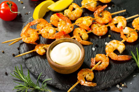 Grilled seafood. Delicious Grilled shrimps with spice, lemon and sauce served on a slate board. Seafood. Stock Photo