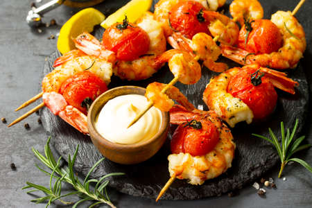 Grilled seafood. Delicious Grilled tiger shrimps with tomatoes, lemon and sauce served on a slate board. Seafood.