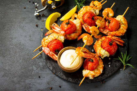 Grilled seafood. Delicious Grilled tiger shrimps with tomatoes, lemon and sauce served on a slate board. Seafood. Copy space.