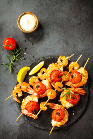 Grilled seafood. Delicious Grilled tiger shrimps with tomatoes, lemon and sauce served on a slate board. Seafood. Top view flat lay background. Stock Photo