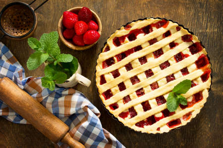 Berry pie summer. Sweet pie, tart with fresh berry strawberries on a rustic kitchen table. Delicious cake with strawberries. Top view flat lay background.