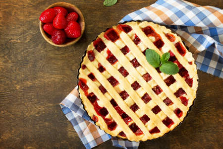 Berry pie summer. Sweet pie, tart with fresh berry strawberries on a rustic kitchen table. Delicious cake with strawberries. Top view flat lay background. Copy space. Stock Photo