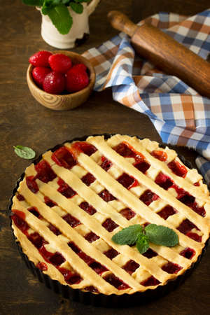 Berry pie summer. Sweet pie, tart with fresh berry strawberries on a rustic kitchen table. Delicious cake with strawberries.   Stock Photo