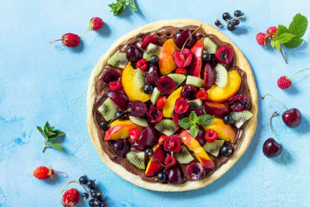 Vitamin dessert. Delicious homemade Summer fruit berry pizza with chocolate paste on a blue stone table. Top view flat lay background.