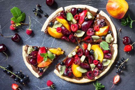 Vitamin dessert. Delicious homemade Summer fruit berry pizza with chocolate paste on a dark stone table. Top view flat lay background. Stock Photo