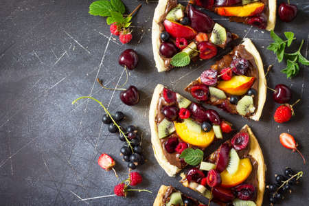 Vitamin dessert. Delicious homemade Summer fruit berry pizza with chocolate paste on a dark stone table. Top view flat lay background. Copy space. Stock Photo