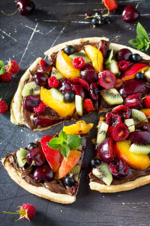 Vitamin dessert. Delicious homemade Summer fruit berry pizza with chocolate paste on a dark stone table.