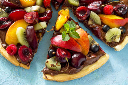 Vitamin dessert. Delicious homemade Summer fruit berry pizza with chocolate paste on a blue stone table.