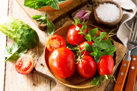 Healthy food: fresh vegetables on the kitchen wooden table. Fresh tomatoes, cucumbers and rucola for cooking salad. Diet menu.