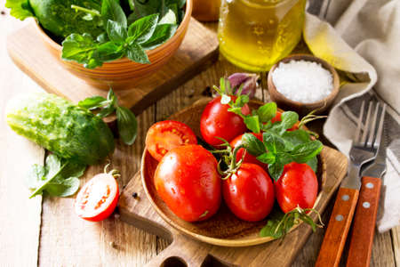 Healthy food: fresh vegetables on the kitchen wooden table. Fresh tomatoes, cucumbers and rucola for cooking salad. Diet menu. Copy space.
