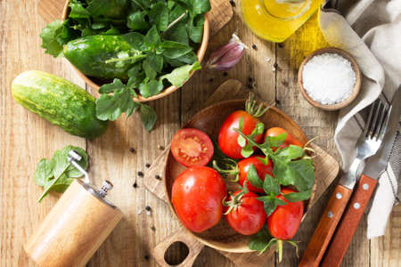 Healthy food: fresh vegetables on the kitchen wooden table. Fresh tomatoes, cucumbers and rucola for cooking salad. Diet menu. Top view flat lay background. Stock Photo