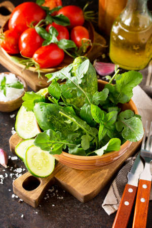 Healthy food: fresh vegetables on a stone table. Fresh tomatoes, cucumbers and rucola for cooking salad. Diet menu.