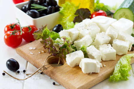 Ingredients for cooking qreek salad with fresh vegetables, feta cheese and black olives on wooden table.