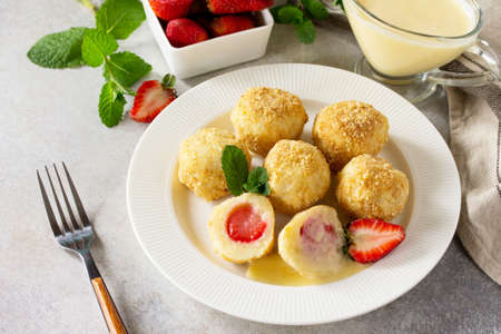 Cottage cheese dumplings with fresh strawberry, served with sour-honey sauce, delicious summer dessert on a bright stone table.