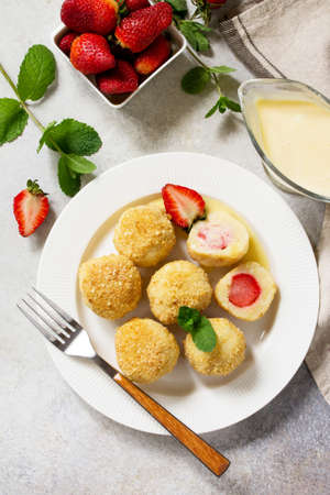 Cottage cheese dumplings with fresh strawberry, served with sour-honey sauce, delicious summer dessert on a bright stone table. Top view flat lay background.