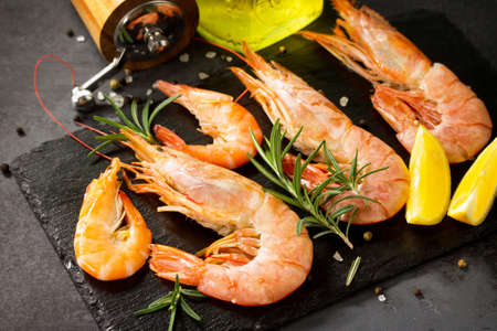Seafood. Raw shrimps with spice and lemon on a slate board.