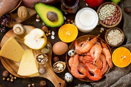 Ausgewogener Lebensmittelhintergrund. Gesundes Essen und Diätkonzept. Proteinnahrungsmittel, Obst, Saft und Gemüse auf einem rustikalen hölzernen Hintergrund. Draufsicht flach legen Hintergrund.