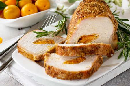 Rouleau de viande (roulade) avec farce aux abricots et épices sur fond de pierre claire ou d'ardoise. Apéritif de jour de Thanksgiving.