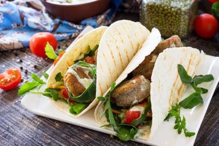 Deliziosa tortilla fresca fatta in casa con falafel e insalata fresca sul tavolo. Tacos vegani. Cibo sano vegetariano. Archivio Fotografico