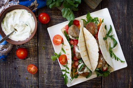 Delicious fresh homemade tortilla wrap with falafel and fresh salad on the table. Vegan tacos. Vegetarian healthy food. Top view flat lay background.