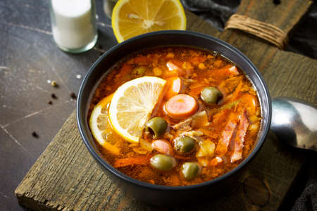 Traditional Russian soup Solyanka with meat, sausages, vegetables, capers, pickles and olives with lemon on black background. Rustic style.   Stockfoto