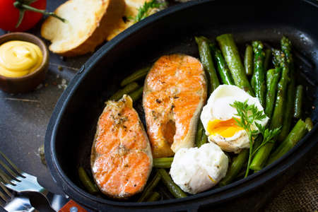 Salmon fish steak grilled with asparagus, poached egg in a frying pan on a rustic stone table. Healthy food.