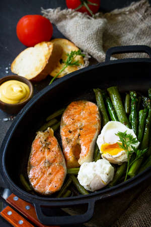 Salmon fish steak grilled with asparagus, poached egg in a frying pan on a rustic stone table. Healthy food. Standard-Bild - 124975290