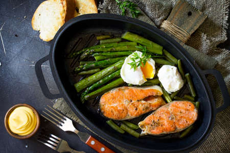 Salmon fish steak grilled with asparagus, poached egg in a frying pan on a rustic stone table. Healthy food. Top view flat lay.  Free space for your text.