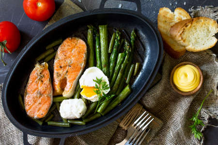 Salmon fish steak grilled with asparagus, poached egg in a frying pan on a rustic stone table. Healthy food. Top view flat lay.