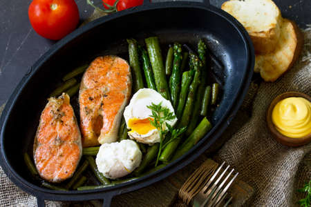 Salmon fish steak grilled with asparagus, poached egg in a frying pan on a rustic stone table. Healthy food. Top view flat lay. Standard-Bild - 124975294