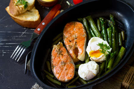Salmon fish steak grilled with asparagus, poached egg in a frying pan on a rustic stone table. Healthy food. Top view flat lay. Standard-Bild - 124975295
